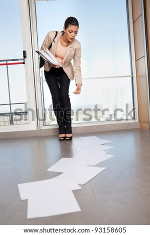 Beautiful business woman bending down to collect scattered papers on floor - stock photo