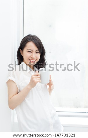 Beautiful business woman drinking coffee at office - stock photo