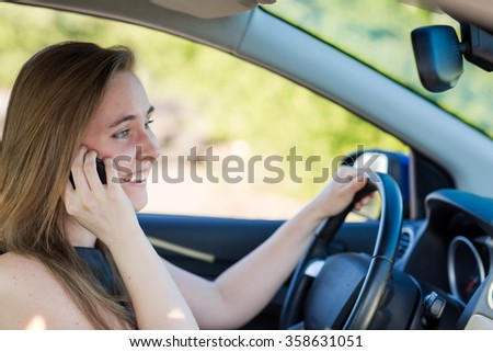 Beautiful business woman driving a car, talking on the mobile phone