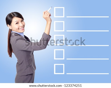 Beautiful business woman Filling Check list in the air (empty copy space great for your design) with blue background, asian model - stock photo