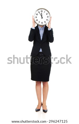 Beautiful business woman hiding behind big clock.