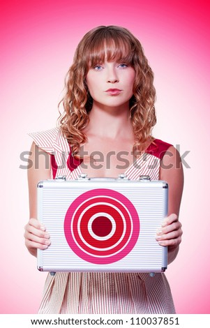 Beautiful business woman holding briefcase with target symbol in a depiction of aim, ambition and purpose - stock photo