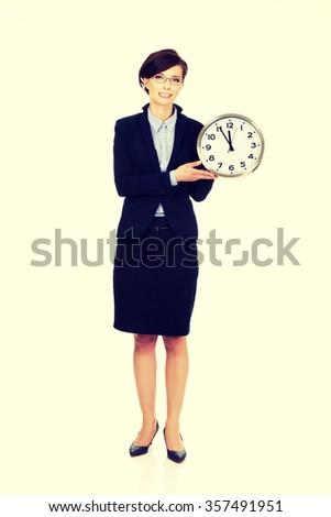Beautiful business woman holding clock in hands. - stock photo