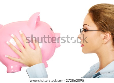 Beautiful business woman holding piggy bank. - stock photo