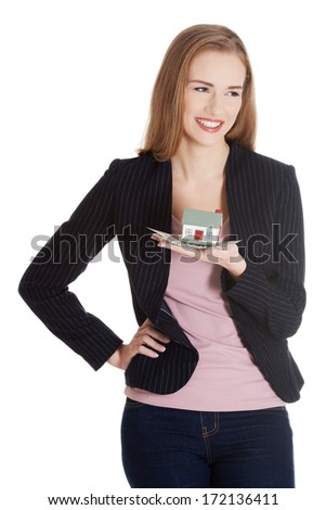 Beautiful business woman holding small house on palm. Isolated on white.
