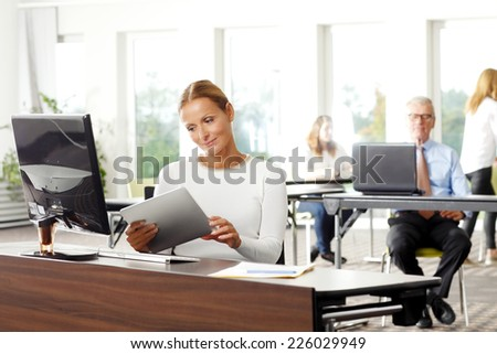 Beautiful business woman holding tablet in her hands, while sitting at office.  - stock photo