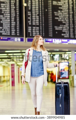 Beautiful business woman in international aiport. Woman preparing to fly. New York airport, USA - stock photo