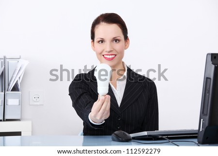 Beautiful business woman in office holding energy saving eco bulb. - stock photo