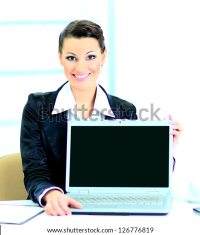 Beautiful business woman in the office, representation of the laptop. - stock photo