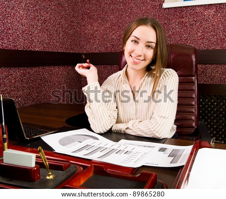 Beautiful business woman is working at the office - stock photo