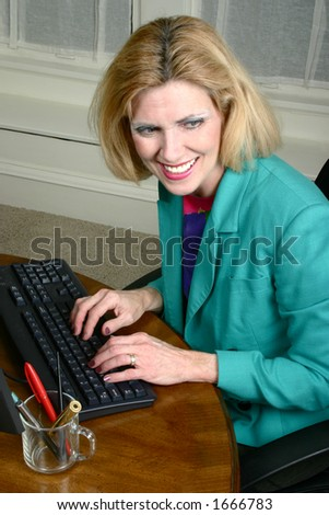 Beautiful business woman laughing with a co-worker neighbor while typing on office computer office. - stock photo