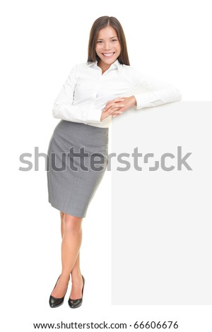 Beautiful business woman leaning on billboard sign in full length isolated over white background. Asian / Caucasian female model.