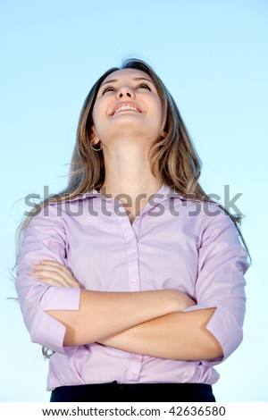 Beautiful business woman looking up with arms crossed - stock photo