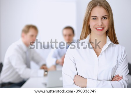 Beautiful business woman on the background of business people during meeting - stock photo