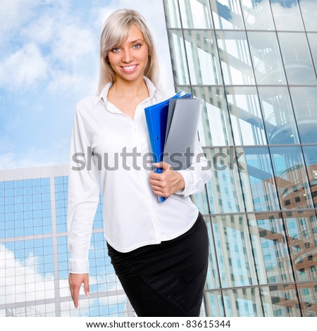 Beautiful business woman on the background of the modern office and the blue sky