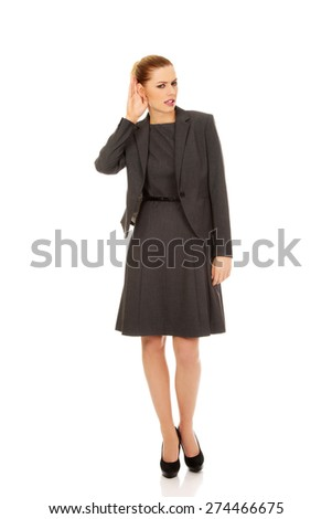 Beautiful business woman overhearing a conversation. - stock photo