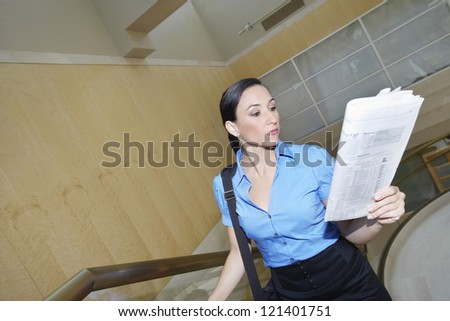 Beautiful business woman reading financial newspaper in office - stock photo
