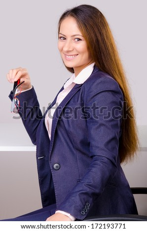 Beautiful business woman sitting at her desk isolated on gray.