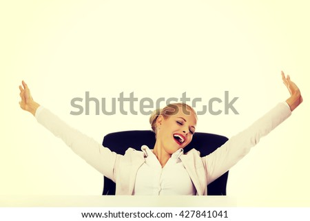 Beautiful business woman sitting behind the desk and stretching her arms - stock photo