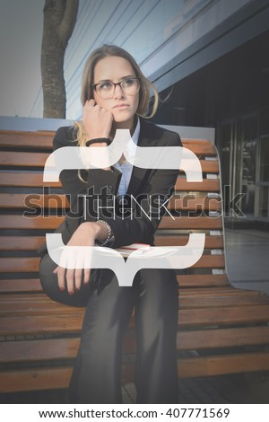 Beautiful business woman sitting on a bench outside her office with think text. - stock photo