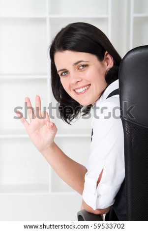 beautiful business woman sitting on office chair looking back and giving ok sign - stock photo