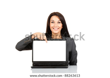 beautiful business woman smile sitting at the desk looking at camera, point finger at isolated white laptop screen over white background