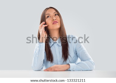 Beautiful business woman talking on cell phone while looking at copyspace at her desk