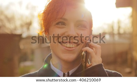 Beautiful business woman talking on mobile phone. Young smiling woman using smartphone. Closeup outdoor portrait of happy girl holding mobile phone, making a call on sunny sunset street.