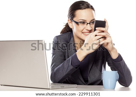 Beautiful business woman texting on the phone at her desk - stock photo