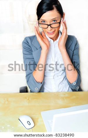 Beautiful business woman thinking about something while working on computer at her office - stock photo