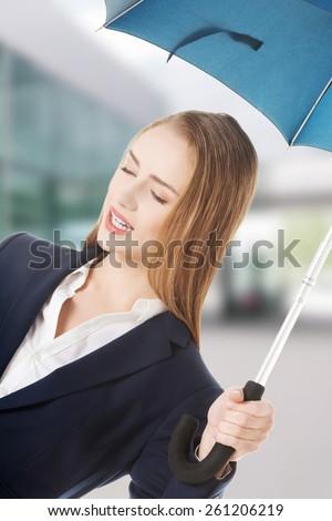 Beautiful business woman under umbrella - stock photo