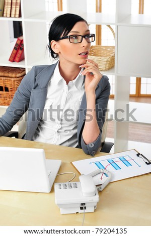 Beautiful business woman wearing eye glasses thinking about something while working on computer at her office - stock photo