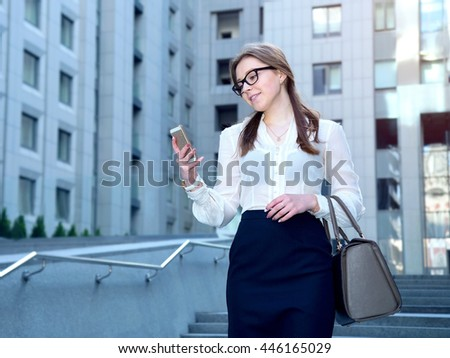 Beautiful business woman wearing glasses and hold smart phone. Woman reads a message on your phone. - stock photo