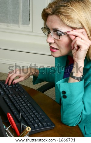 Beautiful business woman wears eyeglasses to look at detail of her work on the office computer. - stock photo