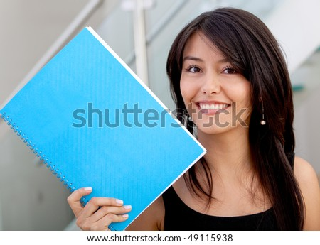 Beautiful business woman with a notebook and smiling - stock photo