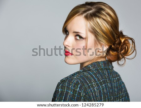 beautiful business woman with blond hair in a bun wearing a tweed jacket and red lipstick on grey studio background - stock photo