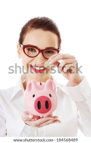 Beautiful business woman with coin and piggy- bank. Isolated on white. - stock photo