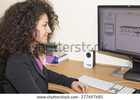 Beautiful business woman with curly dark hair smiling in a studio office.