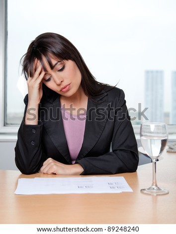 Beautiful business woman with hand on head at workplace - stock photo