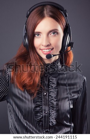 beautiful business woman with headphones against dark grey background - stock photo