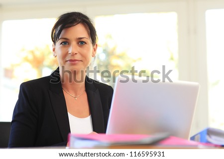 Beautiful business woman with laptop in her office