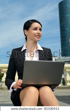 Beautiful business woman with laptop sitting on footstep and working outdoor - stock photo