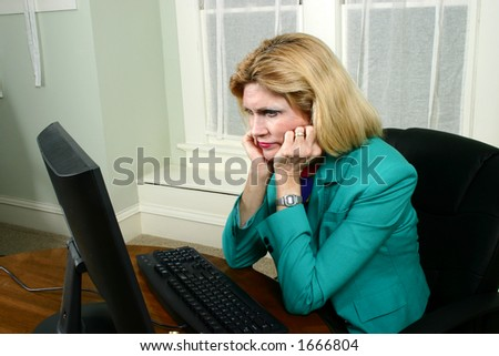 Beautiful business woman, with lips pursed, frustrated and staring at her computer in the office. - stock photo