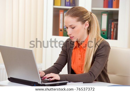 Beautiful business woman working on laptop at office - stock photo