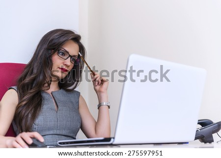 Beautiful business woman working on the computer in her office while she is thinking - stock photo