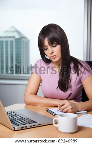 Beautiful business woman writing down some notes in notepad with laptop on desk - stock photo