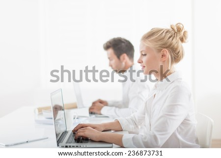 Beautiful businesswoman and her colleague working on computers at office - stock photo