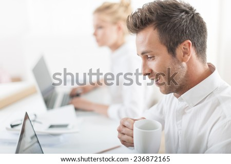 Beautiful businesswoman and her colleague working on computers during a meeting - stock photo
