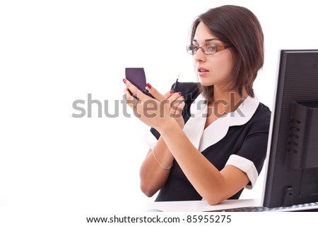Beautiful businesswoman applying lipstick using lip concealer brush in the office - stock photo