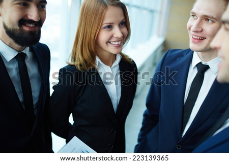 Beautiful businesswoman discussing a project with her male colleagues  - stock photo